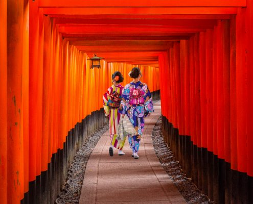 Women in traditional japanese kimonos walking at Fushimi Inari Shrine in Kyoto Japan